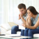 Worried couple reading an important notification in a letter sitting on a couch in the living room at home