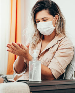 Coronavirus. Woman in quarantine wearing protective mask sanitizing her hands with alcohol gel