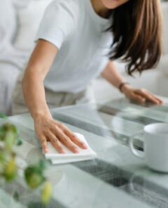 Cropped shot of young Asian woman tidying up the living room and wiping the coffee table surface with a cloth